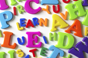 Composition of colorful plastic toy letters and word LEARN
