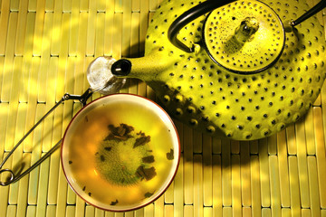 Green asian teapot with cup and green tea