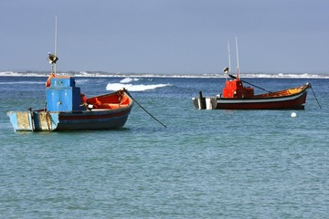 two colourful fishing boats moared in a small harbour