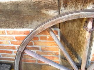 Wagenrad von Pferdekutsche vor einem Fachwerkhaus