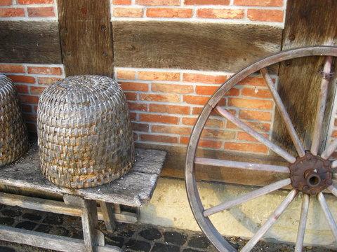 Wagenrad von Pferdekutsche und Bienenkorb vor einem Fachwerkhaus