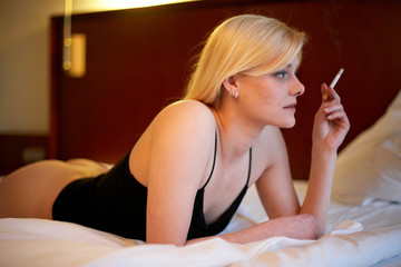 Frau liegt rauchend auf dem Bett