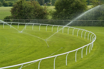 Sprinklers watering a lush green racecourse,