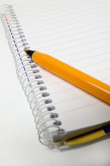 Notepad and yellow pen on white background (focus: pen)