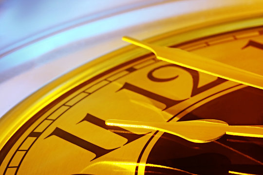 Golden-hued clock, with hands at the eleventh hour.