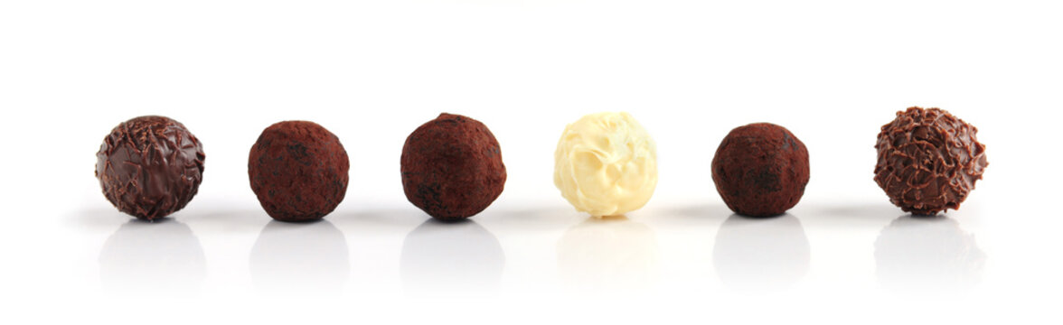 Row of assorted chocolate truffles on white background