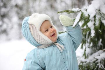 Winter joy - small kid stands next to snowy tree