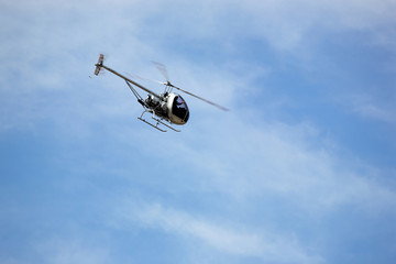 The helicopter on a background of the blue sky