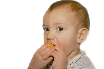 baby boy eatng orange, isolated over white