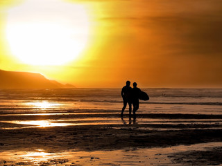 Silhouette of a male and female surfer