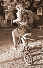 young boy in old style clothing rides a tricycle
