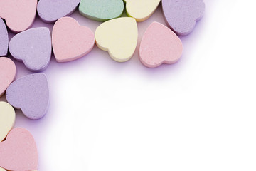 Colorful candy sweet hearts around edges of white