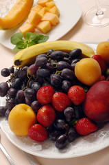 Apricots, banana, grapes and strawberries on plate