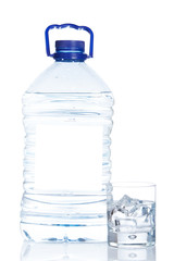 Bottle and glass of mineral water reflected on white background