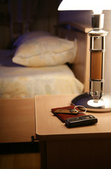 Keys and the passport on a bedside-table in hotel