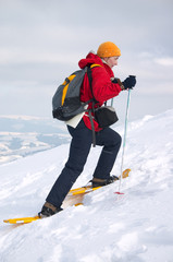backpacker girl in snow shoes moving up on snow slope