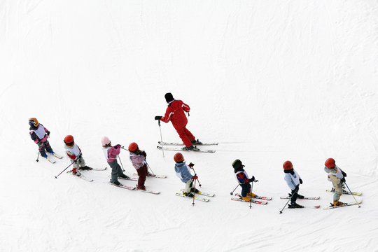 winter scene: kids learning to ski and their instructor