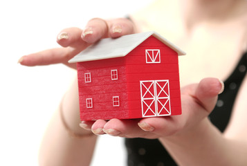 The red house is in a female hand on a white background