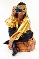Sexy girl with old photo camera sitting on a pouf.