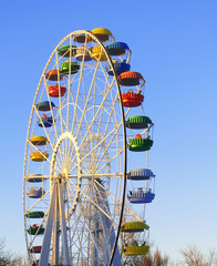 Big colorful ferris wheel over blue sky
