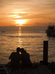A couple cuddling on a dock Koh Tao Thailand