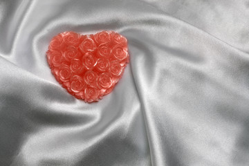 Heart-shaped candle on white satin, with space for text