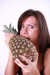 Girl bites in really big pineapple, symbol of health