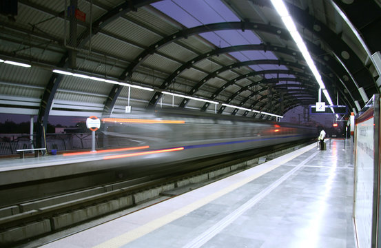 metro zooming past station, delhi, india
