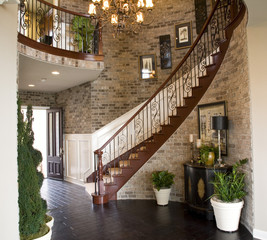 Mansion hallway with a winding staircase.