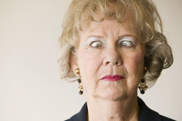 Close-up of a senior woman crossing her eyes.