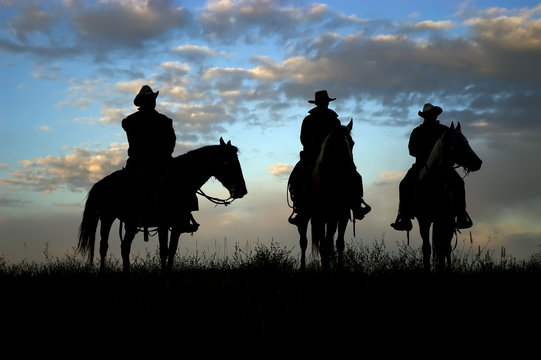 Three cowboys on horseback silhouetted against dawn sky