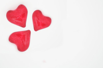 Three red glitter hearts isolated on white