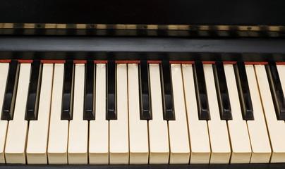 Antique piano with yellowish and dirty old keyboard