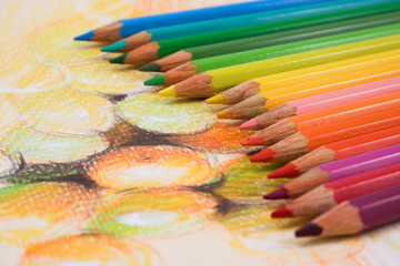 Assortment of coloured pencils on draw background