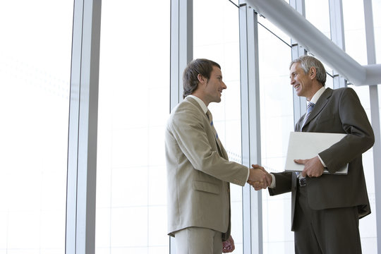Businessmen shaking hands in front of large glass windows