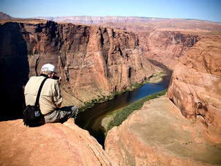 An eldery man hangs his legs off a cliff to get a picture