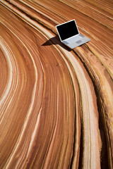 A silver laptop sits on top of a rock formation
