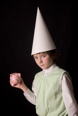 Sad young boy in a dunce cap with a piggybank