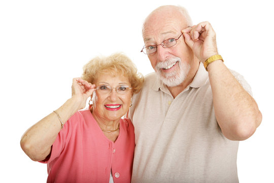 Attractive senior couple wearing glasses.  Isolated on white.