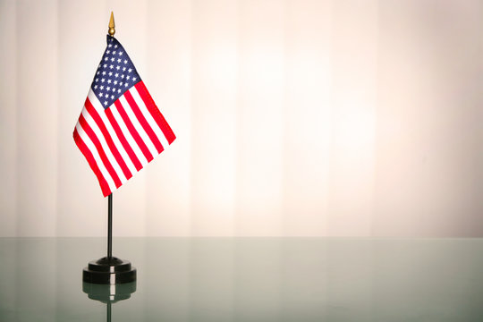 American flag on a glass table, office like setting; copyspace