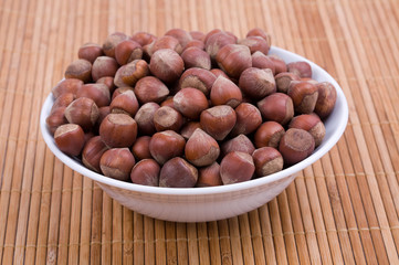 Hazelnuts in a white bowl on rush mat