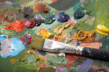 Paintbrush on colorful painting palette. Shallow DOF..