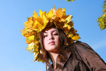 Wall Mural - Beautiful young woman in crown of golden autumn leaves.