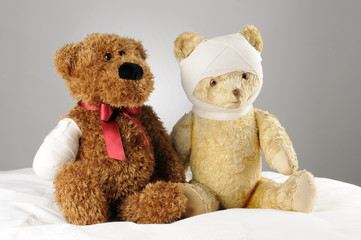 two injured teddy bears holding each other