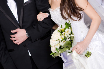 hands of a groom and a bride with a wedding flower bouquet