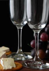 Two empty wine flutes by grapes and brie cheese,