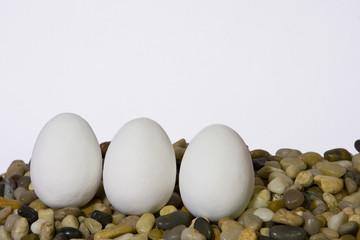 Three white easter eggs on pebbles against white background