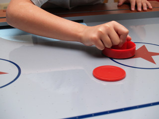 hand on a mallet on an air hockey table