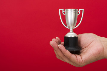 Trophy in hand on red background with copy space
