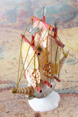 Sailing ship made from seashells over old map